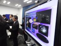 小惑星探査機はやぶさ2の地球スイングバイ成功の記者会見で公開された「はやぶさ2からのクリスマスカード」。モニターの左は吉川真ミッションマネジャー、その向こうが津田雄一プロジェクトマネジャー=東京都千代田区の宇宙航空研究開発機構で2015年12月24日、永山悦子撮影