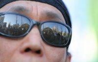 安保関連法制の廃止と安倍政権の退陣を訴える集会に参加した男性。サングラスには国会議事堂が反射していた=東京都千代田区で2016年1月4日午後1時、後藤由耶撮影
