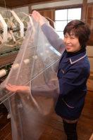「フェアリー・フェザー」で作られたストールを広げる斎栄織物の従業員=福島県川俣町の同社工場で