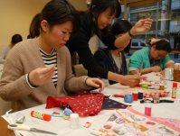 ワークショップでランチバッグの作り方を教えるHOUKOさん(中央)=横浜市のカフェ「ペガサス」で、野村房代撮影