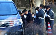 棺を乗せて遺体安置所を出発する車を見送る警察官ら=長野県軽井沢町で2016年1月16日午前9時53分、後藤由耶撮影