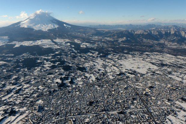 山頂に雪をかぶった富士山と白く染まったふもとの町=2016年1月19日午後3時33分、本社ヘリから徳野仁子撮影<br />