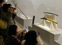 スマホやカメラを手に展示されている「圧切長谷部」(右)に見入る女性たち=福岡市早良区で2016年1月20日、山下恭二撮影