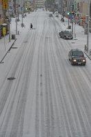 雪で白くなった道路を走る車=北九州市小倉北区で2016年1月24日午前9時19分、矢頭智剛撮影