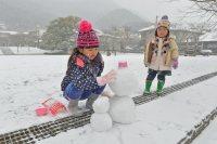 積もった雪で雪だるまを作る子どもたち=北九州市小倉北区で2016年1月24日午前11時30分、矢頭智剛撮影