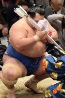 豪栄道を突き落としで降して優勝を決め、懸賞の束を額に寄せる琴奨菊=東京・両国国技館で2016年1月24日、内藤絵美撮影
