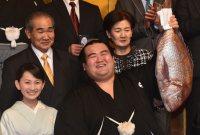 タイを手に笑顔を見せる優勝した琴奨菊(手前右)左は妻・祐朱さん。後ろは父・一典さんと母・美恵子さん=東京都内のホテルで2016年1月24日午後7時12分、竹内幹撮影