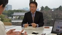 オリンパスの損失隠し事件を2011年にスクープした山口義正さん。手前は今沢真・経済プレミア編集長