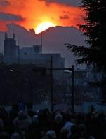 旧国立競技場が取り壊され、神宮外苑から臨む富士山(右上)に沈む夕日。多くの人がダイヤモンド富士を一目見ようと集まった=明治神宮外苑で2016年2月4日午後4時59分、長谷川直亮撮影