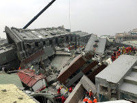 地震で崩壊したマンション。消防隊員らが取り残された住民などの捜索、救出作業を懸命に行っていた=台湾南部の台南市で2016年2月6日、鈴木玲子撮影