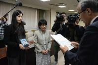 松竹君の遺影を掲げ第三者委の報告書を受け取る遺族の代理人弁護士たち=長崎市で1月6日、小畑英介撮影