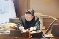 6日に「人工衛星打ち上げ」に関する文書に署名する北朝鮮の金正恩第1書記=朝鮮中央通信・朝鮮通信