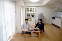 引っ越し直後のようにモノの少ない部屋で暮らす野崎未和さんと塚本泰久さん=奈良市で、中本泰代撮影