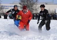 積もった雪をかき分けて、相手陣地へ突進する選手=千歳市のキリンビール北海道千歳工場で2016年2月7日、野原寛史撮影