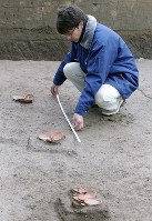 飛鳥寺西方遺跡で見つかった祭祀跡。3カ所に重ねた皿が直線上に並んでいた=奈良県明日香村で2016年2月9日、三村政司撮影