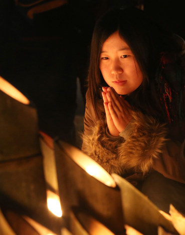 Honoka Shino presses her palms together in front of bamboo lanterns honoring those who died in the 1995 Great Hanshin Earthquake on the 21st anniversary of the disaster on Jan. 17, 2016. (Mainichi)
