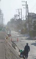 震災による液状化で電柱が傾き、道路が波打った浦安市内=2011年3月26日、小林努撮影