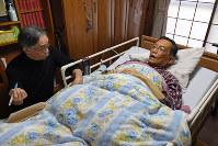 在宅で緩和ケアを受けることを選んだ末期がんの西浦明彦さん(右)。診療に訪れた山崎章郎医師の問診に、自ら体調の変化を説明していた=東京都小平市で、竹内紀臣撮影
