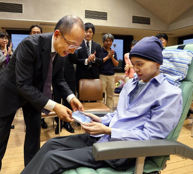 昨年5月、三谷さんからCDを受け取る旭さん(右)=神奈川県鎌倉市で、小出洋平撮影