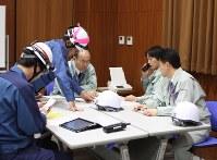 柏崎刈羽原発の事故対策訓練で、東電職員(左の2人)から説明を聴く刈羽村職員=同村役場で