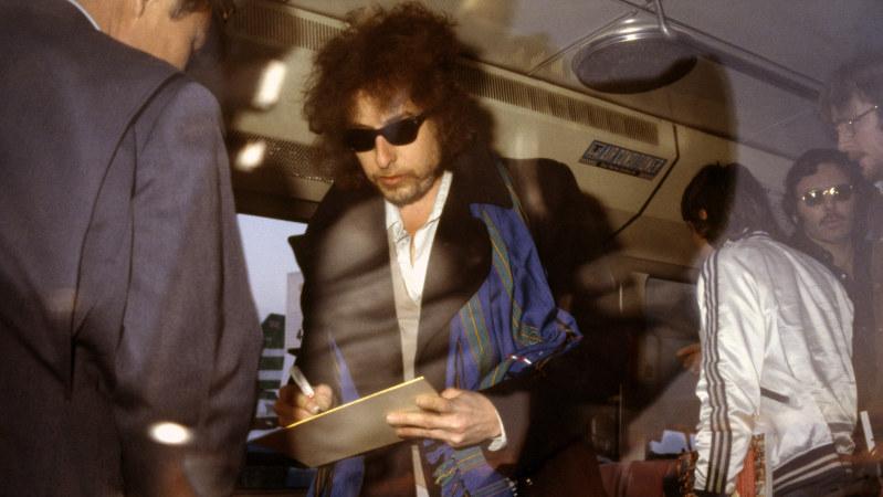 羽田空港に到着してバスの中で運転手の求めに応じてサインするボブ・ディラン=1972年2月撮影