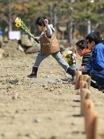 祖母が仮埋葬されている576番の木札の前に花を手向けた斎藤佑星君(中央)。父知文さんと母るみ子さんが見守っていた=宮城県石巻市で2011年4月10日、梅村直承撮影