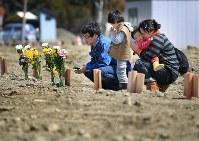 仮埋葬されている祖母と叔父に手を合わせる斎藤佑星君、、知文さん、るみ子さん、妹のあかりちゃん。自宅が全壊、避難所から訪れた=宮城県石巻市で2011年4月10日、梅村直承撮影