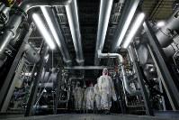 配管が網の目のように頭上を覆う冷凍機のある建屋=福島第1原発で、森田剛史撮影