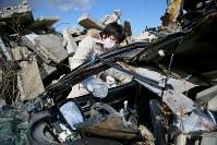 いまだに行方不明の夫健一さん(当時41歳)が運転していた車のハンドルに水をかける佐藤久美子さん(35)。原発事故による避難指示で、これまで十分な捜索ができず、車は昨年9月11日、健一さんの眼鏡と共に初めて見つかった。幼い息子2人をよく世話する子煩悩な夫だった。「早く見つかってほしい。そうでなければ気持ちの区切りがつかない」=福島県浪江町で2014年3月11日午前11時15分、森田剛史撮影