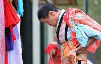 真紀子さんが作ってくれた衣装に袖を通す千葉文彦さん(65)。なれた手つきで着物を着た=宮城県石巻市で2015年9月20日、小川昌宏撮影