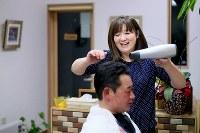 内陸部で営業するようになった「澤とこや」で、夫豊明さんの小学生の頃からの友人、川原貴義さん(51)を整髪し、笑顔を見せる澤純子さん。鐵男さんと親子3人で営んでいた震災前のお店は「お茶っこ」する人などでいつもにぎやかだった。川原さんは「見つかって本当に良かった。『とよ』は他にいないくらい人がいいから、何かあれば(助けに)行ってしまう」。豊明さんが上手な踊りを披露した祭り、よく一緒に行ったスキー。思い出話に花が咲いた=岩手県大槌町で2016年2月26日、森田剛史撮影