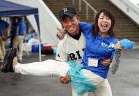高校最後の公式戦を終え、晴れ晴れとした表情で母・吏佳さん(43)を抱き上げる高橋禎希さん(18)。南三陸町の防災対策庁舎で津波に流されて今も行方がわからない父・文禎さん(当時43歳)に代わり、吏佳さんは一家の家計を支え、週末は1時間以上かけて利府高校野球部に所属する禎希さんの試合や練習に駆けつけた。「それでも、僕には疲れた顔一つ見せなかった」。同じ球児だった父に教わって始めた野球。最後の試合、禎希さんは代打で出場してヒットを放ち、試合後は「やりきった」とすがすがしい表情を見せた。4月には関東の大学へ進学し、得意の英語を専攻する。いずれは南三陸町に戻り、子供たちに野球を教えることも夢の一つだ。しかし、故郷は若者を中心に人口流出が続き、少年野球チームを成立させるのもぎりぎりの状態。将来、町へ戻るか、否か。「今はまだわからない」=宮城県石巻市で2015年7月17日、喜屋武真之介撮影
