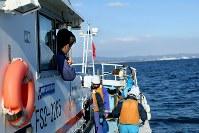 震災直後、津波から船を沖に出して守った一方、長女柑那ちゃん(当時1歳半)が流され行方不明になった相馬双葉漁協富熊支所長の石井宏和さん(39)。福島第1原発の汚染水問題に悩まされながらも試験操業が進むなか、営んでいた釣り船業は風評被害などからいまだ再開できず、水質調査のために沖に出した船から、以前の操業海域だった原発(右奥)周辺の海を見つめていた。「何のために船を守ったのか」。自責の念に駆られる日々から、震災後に2人の子どもを授かり「救われた」。「次の世代のためにも」福島の海と生きていくことを決めた=福島県いわき市で2016年2月17日、森田剛史撮影