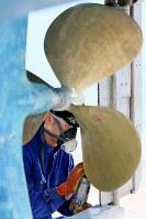 所有する釣り船「長栄丸」を陸に上げ、船底の舵などを塗装する相馬双葉漁協漁協富熊支所長の石井宏和さん(38)。福島第1原発事故の影響でヒラメやアイナメなど主力魚種はいまだ出荷できず、釣り船業は自粛を続ける。モニタリング漁などで船を海に出す機会は月3回ほどに激減。「船の異変にも気付かなくなった」。津波から船を沖に出して守ったが、長女柑那ちゃん(当時1歳半)は行方不明のまま。「船を守ったことは何だったのか」と自問する=福島県いわき市の久之浜港で2015年4月12日、森田剛史撮影