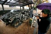 津波にのまれ行方不明になった警察官の長男雄太さん(当時24歳)が乗っていたパトカー前に設置されたポストの中を確認する佐藤安博さん(56)。震災の惨禍を後世に伝えるために町内の公園に展示され、ポストに寄せられる手紙などはこれまでに700通を超えた。しかし、年々その数は減り、佐藤さんは「震災の風化を感じている」=福島県富岡町で2015年11月8日、森田剛史撮影