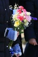宮城県女川町の七十七銀行女川支店では行員ら4人が死亡し、8人が今も見つかっていない。成田絵美(当時26歳)さんもその一人で、父正明さん(59)と母博美さん(55)は一人娘を探している。宮城海上保安部による海中捜索の日、絵美さんが好きだった赤いカーネーションが入った花束を託した。「4年が過ぎても運命だったなんて受け入れられない」と話す博美さん。手を握り、祈るように捜索を見守っていた=宮城県女川町で2016年1月11日、佐々木順一撮影