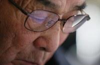 集まった1人1人の署名に目を落とす吉田税さん(81)。「こんなに集まるとは予想していなかった」。眼鏡にはうっすらと白い署名用紙が映った=岩手県陸前高田市で2016年2月17日、小川昌宏撮影