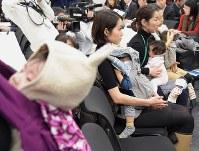 会場に生中継された衆院厚生労働委員会の民主・山尾志桜里氏と塩崎恭久厚労相の質疑を見る出席者ら=東京都千代田区の衆院第2議員会館で2016年3月9日午前11時58分、藤井太郎撮影
