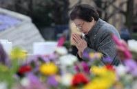 東京大空襲の犠牲者を追悼するため東京都慰霊堂で供花し、手を合わせる女性=東京都墨田区で2016年3月10日午前8時25分、後藤由耶撮影