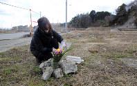 実家の跡地を訪れ、花を手向ける高橋枝美子さん(58)。義父と次女を亡くし、父母はまだ行方不明のままだ。「どこにいるのかな」とつぶやいた=岩手県陸前高田市で2016年3月11日午前11時41分、小川昌宏撮影