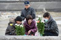 津波で流された請戸郵便局の跡地に花を手向ける福島県二本松市の吉田朝(つとし)さん(中央奥)と妻・聖子さん(同手前)ら。同郵便局に勤めていた長女・美紀さんを亡くした。朝さんは「5年経っても何も変わらない。遺族にとっては区切りなんてない」と話した=福島県浪江町で2016年3月11日午前10時14分、山崎一輝撮影