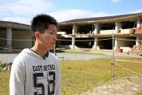 被災した大川小学校(後方)に東松島市から3時間半掛けて自転車で訪れた中学3年生の高橋龍さん。「生きていたらみんな友だちになれたかもしれない。こうして生きている事が幸せだと感じました」と手を合わせていた=宮城県石巻市で2016年3月11日午後0時55分、梅村直承撮影