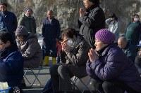 岩手県山田町船越の小谷鳥地区にある漁港で遺族たちが集まり経があげられ、涙をぬぐう川村ケイさん(82)(中央)。同地区で一緒に暮らしていた夫の岩雄さんと息子の勝弘さんが津波で行方不明のまま。「5年たっても涙が出てくる。会いたい」と話した。同地区では18人が津波で亡くなり、見つかっていない人が多い=岩手県山田町で2016年3月11日午後3時8分、和田大典撮影