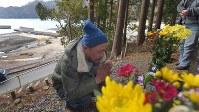 岩手県山田町船越の小谷鳥地区で、津波の犠牲者のために建てられた慰霊碑の前で手を合わせる久保田輔さん(34)。一緒に住んでいた妻とその母、3人の子供たちが津波で行方不明のまま。今は県外で働いているが、毎年3月11日はここで「元気だよ」と手を合わせる。「今でも一緒だった頃の夢を見ることがある。5年たって節目とかってのはない」。同地区では18人が津波で亡くなり、見つかっていない人が多い=岩手県山田町で2016年3月11日午前11時4分、和田大典撮影