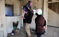 両親と弟を亡くした米沢祐一さん(51)=左=は娘の多恵ちゃん(5)=中央=を連れ、かさ上げ工事地域に残ったビルを訪れた。自身が屋上に上って助かった場所に行き、多恵ちゃんに震災の話をした。米沢さんは「何気なく伝えてきたけど、(今日の話を)理解してくれてうれしかった。子供の世代にも伝えていきたい」=岩手県陸前高田市で2016年3月11日午後2時43分、小川昌宏撮影