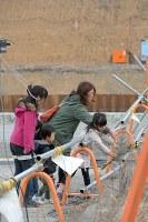 4人の子どもと一緒に、立ち入り禁止区域内に花を手向ける簗瀬絵美さん(35)。花を手向けた場所の先には実家があったが、工事で跡地には近づけなくなった。実家に住んでいた両親と祖母、弟の4人が津波で亡くなり、「実家のそばに行けば会える気がした。行けなくなって辛い」=宮城県南三陸町で2016年3月11日午後4時11分、喜屋武真之介撮影