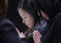 追悼式で献花し、手を合わせる遺族たち=宮城県七ケ浜町で2016年3月11日午後4時3分、猪飼健史撮影