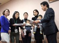 子育て中の母親から署名簿を受け取る塩崎恭久厚労相(右端)=国会内で3月9日、藤井太郎撮影