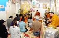 僧侶の食事中にお経を唱える在家信者=東京都八王子市のプッタランシー森林寺院で、棚部秀行撮影