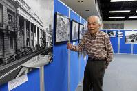 阪神大震災前と後で姿を変えた建物の写真を前に話す米田さん=神戸市中央区のこうべまちづくり会館で